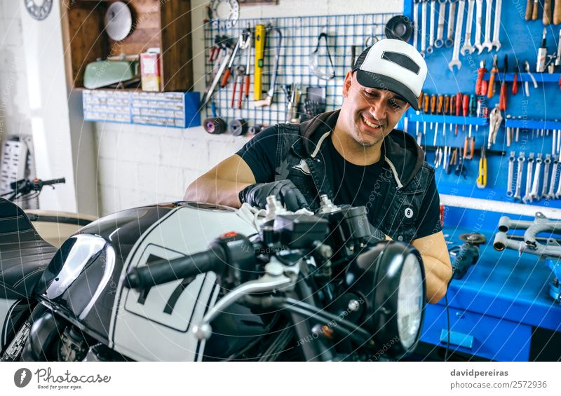 Mechanic cleaning a motorcycle Lifestyle Style Happy Work and employment Engines Human being Man Adults Vehicle Motorcycle Cloth Smiling Authentic Retro vintage