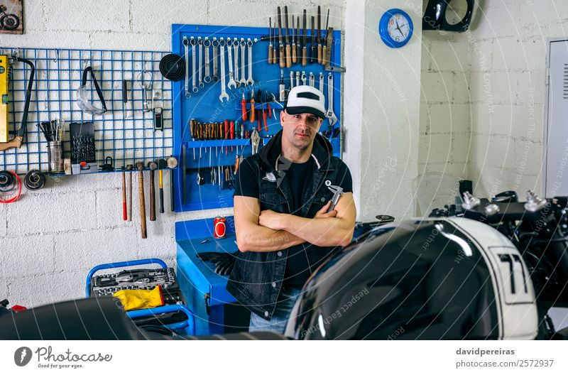 Mechanic posing with a motorcycle Lifestyle Style Work and employment Engines Human being Man Adults Vehicle Motorcycle Authentic Retro Black Pride Earnest