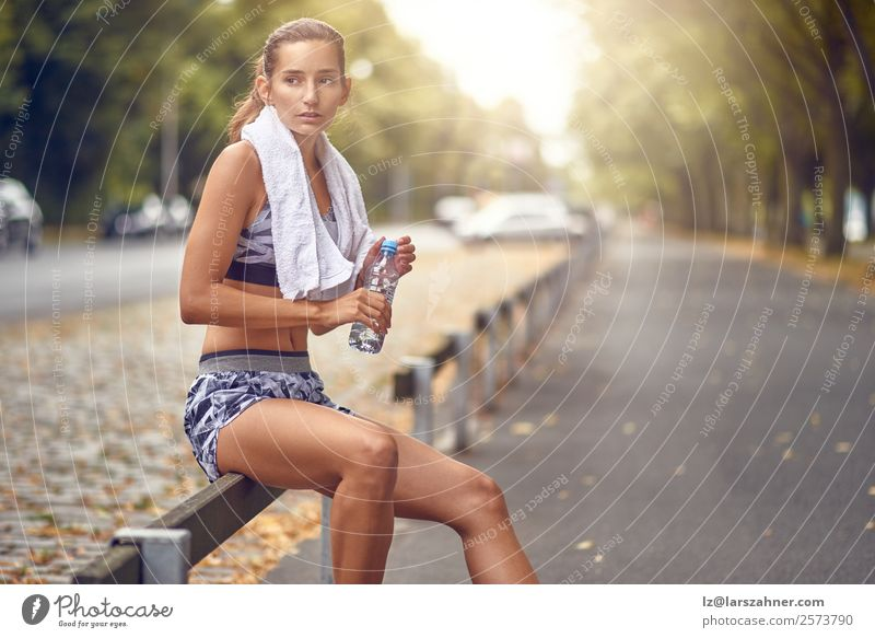 Happy fit woman taking a break from jogging Drinking Lifestyle Summer Sports Jogging Woman Adults 1 Human being 18 - 30 years Youth (Young adults) Warmth Street
