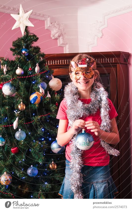 Young girl decorating Christmas tree, holding big Christmas ball. Teenage blonde girl wearing blue jeans skirt and pink blouse and tights. Girl has a funny reindeer mask on her face. Young girl celebrating Christmas at home