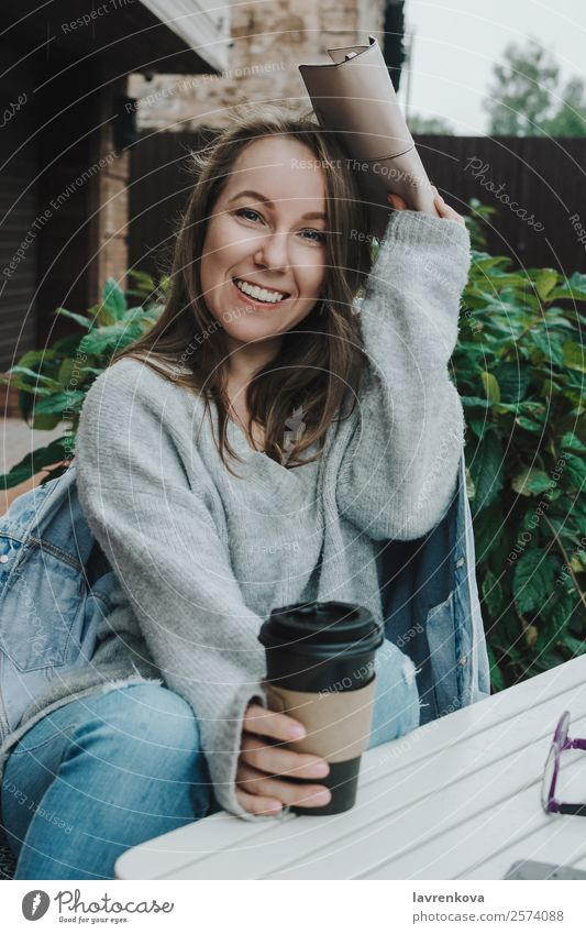 Lifestyle portrait of young female in grey sitting outdoors Rain hiding Covering Handbag Sweater Denim Jeans PDA Warmth Happy Relaxation Safety (feeling of)