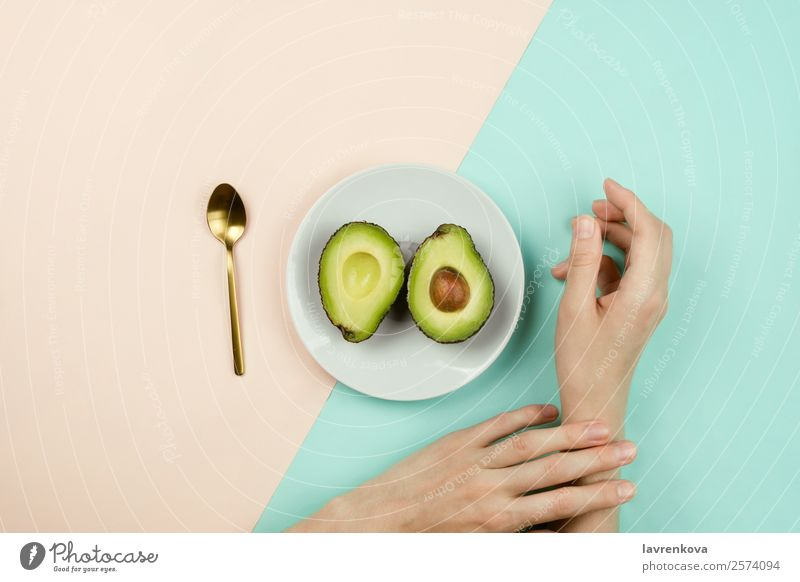 Flatlay with cut avocado on white plate and woman's hands Spoon Vegetarian diet Vegan diet Fruit Eating flat lay Plate Ingredients Diet Healthy Eating