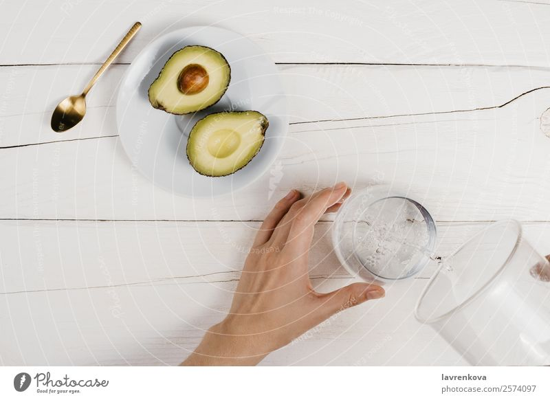 Flatlay of fresh ripe cut avocado halves and woman pouring water Woman Hand Cup Vegetarian diet Vegan diet flat lay Gold Spoon Organic Avocado Breakfast Dinner