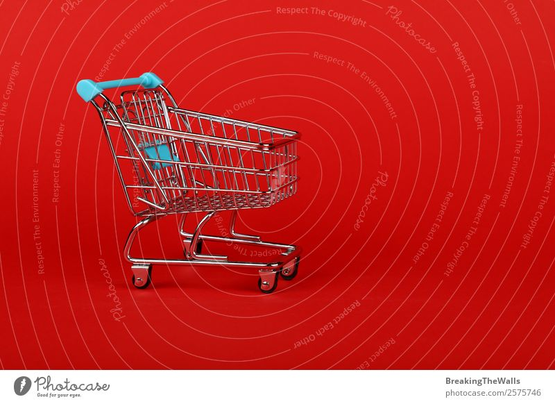 Close up empty toy supermarket shopping cart over red Shopping Economy Trade Logistics Business Toys Metal Plastic Red Colour Retail sector Supermarket Side