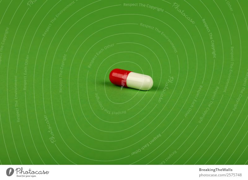 Close up one red and white gel cap pill of medicine on green Colour Green White Red Healthy Background picture Natural Health care Soft Medication