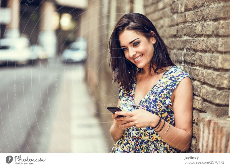 Smiling young woman using her smart phone outdoors Woman Human being Youth (Young adults) Young woman Beautiful White Joy 18 - 30 years Street Lifestyle Adults