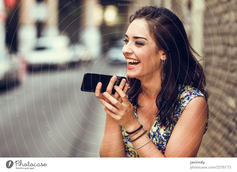 Smiling young woman recording voice note in her smart phone outdoors. Lifestyle Style Happy Beautiful Hair and hairstyles Telephone PDA Technology Human being