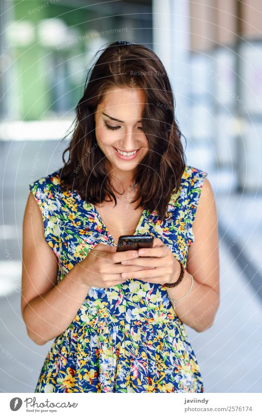 Smiling young woman texting with her smart phone Lifestyle Style Happy Beautiful Hair and hairstyles Telephone PDA Technology Human being Feminine Young woman