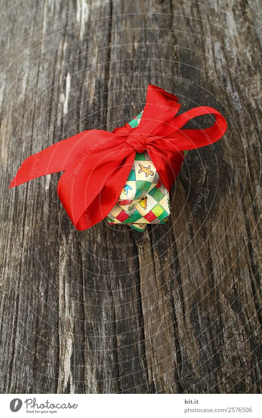 Christmas present with red bow on wood Living or residing Feasts & Celebrations Christmas & Advent Decoration Kitsch Odds and ends Brown Multicoloured Red Joy
