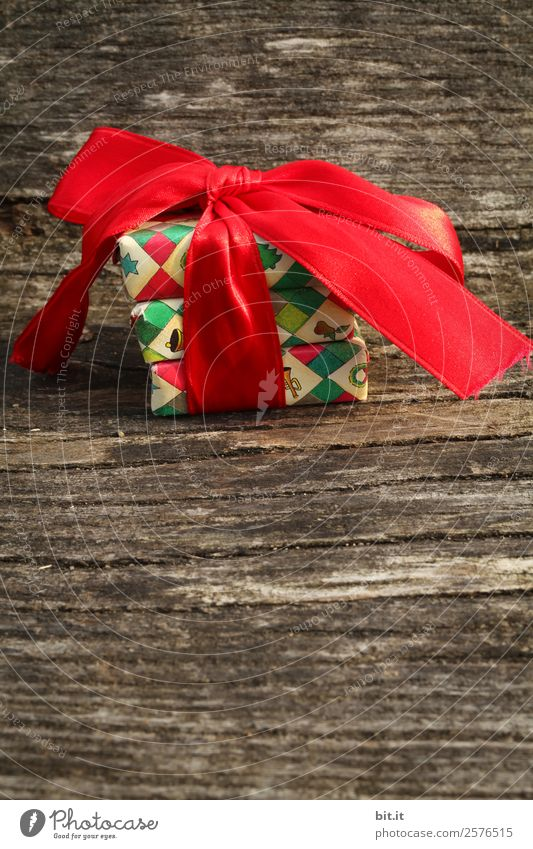 Surprise l colorful Christmas parcels packed with Christmas paper with red bow, lying on rustic wood. Christmas presents, lie nicely decorated with ribbon on wooden table. Many Christmas parcels packed with wrapping paper with Christmas motif.