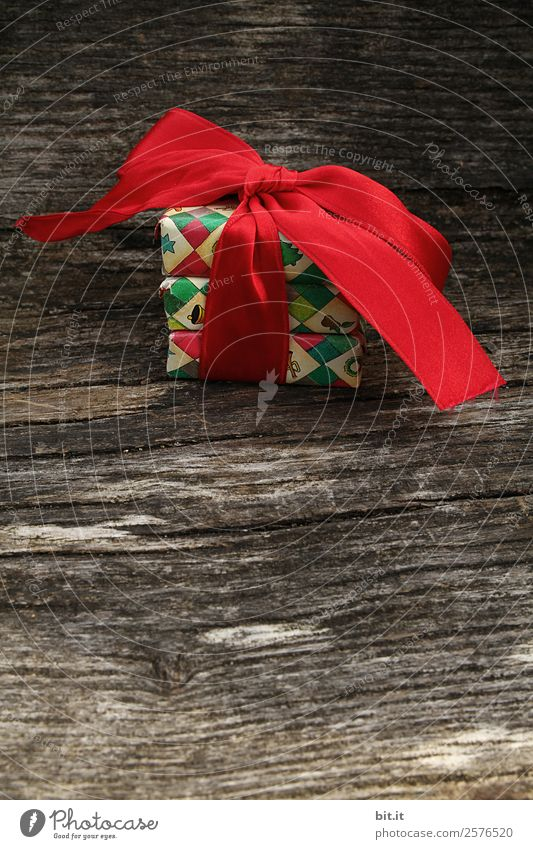 colourful christmas parcels packed with christmas paper with red bow, on rustic wood. Christmas presents, lie nicely decorated with ribbon on wooden table. Many Christmas parcels wrapped with wrapping paper with Christmas motif. Concept gifts Advent.