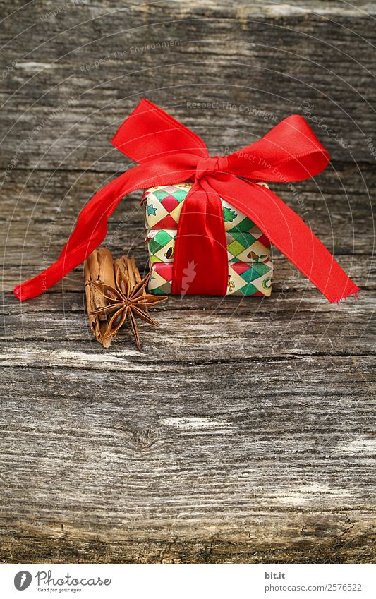 Surprise l colorful Christmas parcels wrapped with Christmas paper with red ribbon, cinnamon, star anise lie on rustic wood. Christmas present, lies nicely decorated with a big bow of red ribbon and christmas spices on a wooden table.