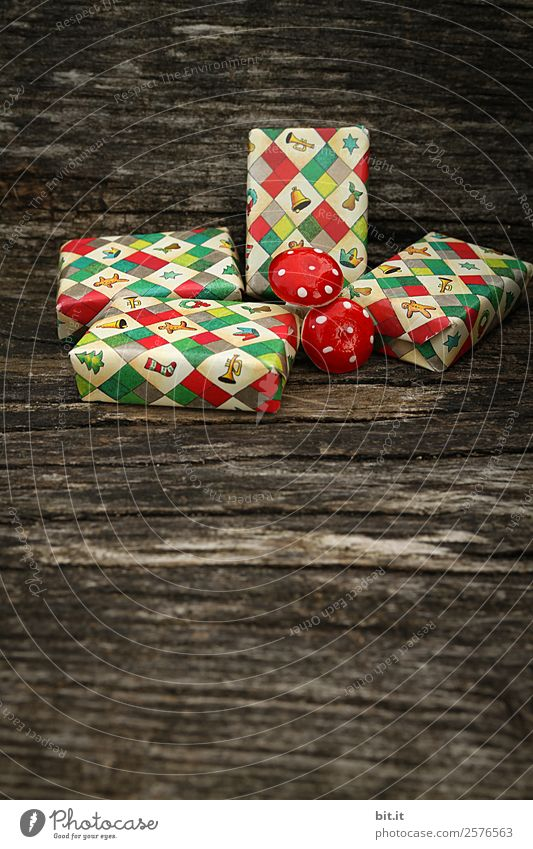 Surprise l many, colorful, wrapped Christmas parcels & mushrooms, lying on old rustic wooden table as decoration and ornamentation. Small Christmas presents wrapped in wrapping paper with a Christmas motif are waiting to be unwrapped under the Christmas tree.