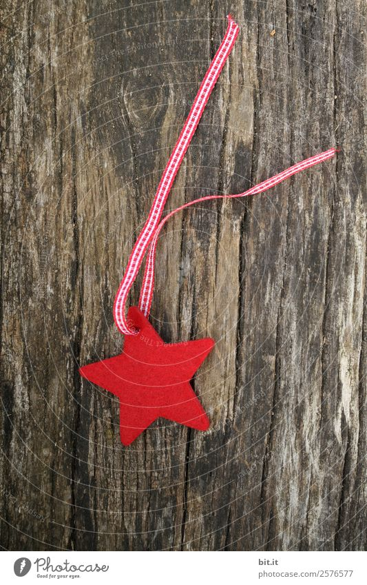 Merry Christmas. Red star of felt with ribbon, lies on old wood. Red checked Christmas star, as decoration on rustic brown wooden board. Felt fabric star as sign, blank, pendant, hanger on brown, rustic wooden table, text space.