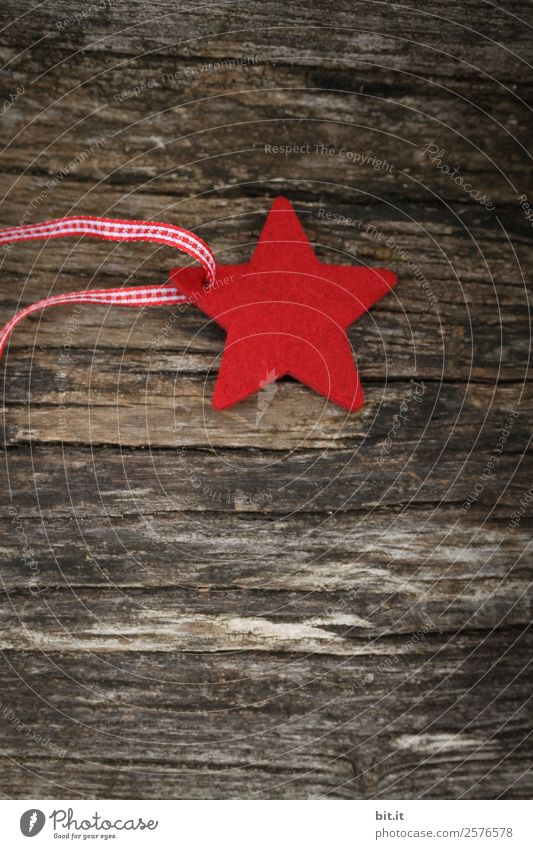Red star made of felt with plaid band, lies on old wood. Red poinsettia, as decoration on rustic brown wooden board. Star as a shield, Christmas tree pendant, gift pendant made of fabric for the Advent season, Christmas time with ribbon with checkered band.