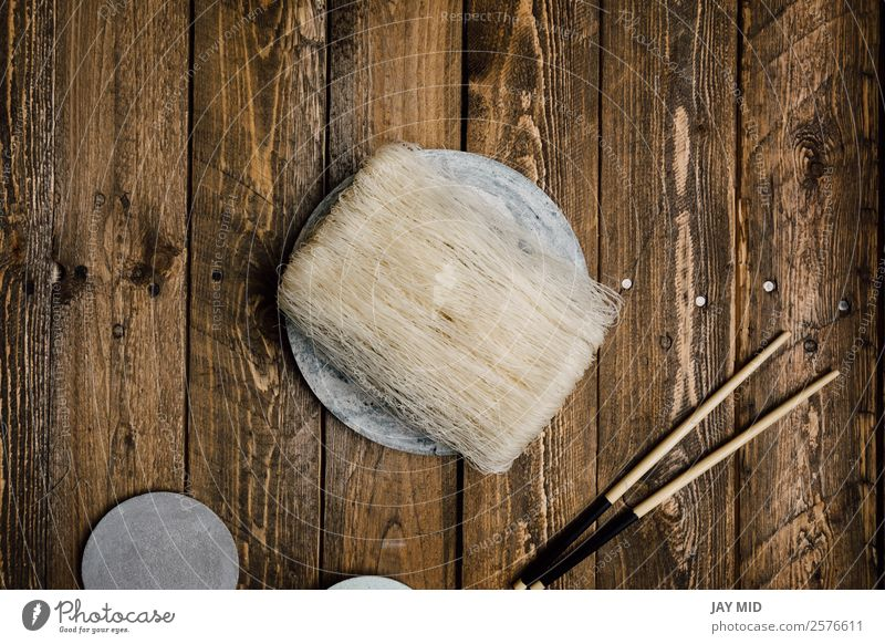Uncooked Asian rice noodles on wood background Diet Asian Food Plate Table Culture Wood White Tradition Noodles Raw Thai food asian pasta dry oriental glass