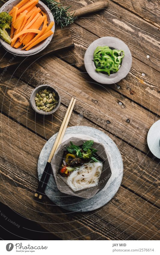 Geometric bowl of Asian Noodle Soup with chopsticks Food Meat Vegetable Stew Lunch Dinner Asian Food Bowl Table Wood Fresh Delicious Green noodle asian Noodles