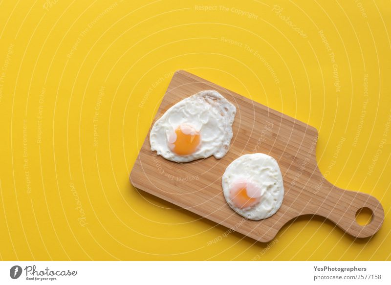 Friedd eggs on a cutting board Food Nutrition Breakfast Lunch Diet Plate Fresh Healthy Bright Delicious Sweet Warmth Yellow above view Cooking Copy Space