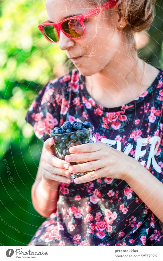 Happy girl enjoying eating the fresh blueberries Human being Youth (Young adults) Young woman Summer Blue Eating Lifestyle Food Natural Garden Fruit Nutrition