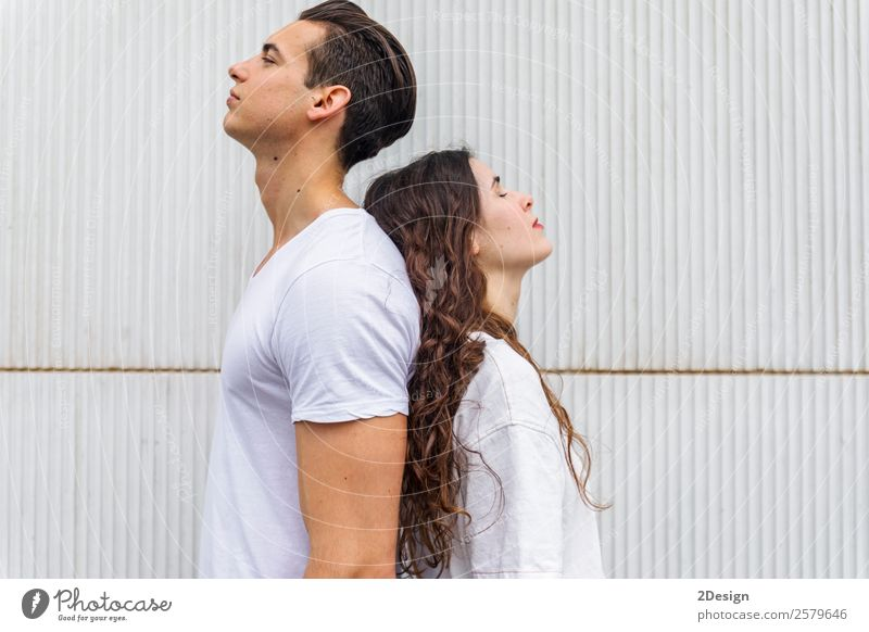 Portrait of a young couple back to back on a white wall Woman Human being Youth (Young adults) Man Summer Joy Black 18 - 30 years Street Adults Love Couple