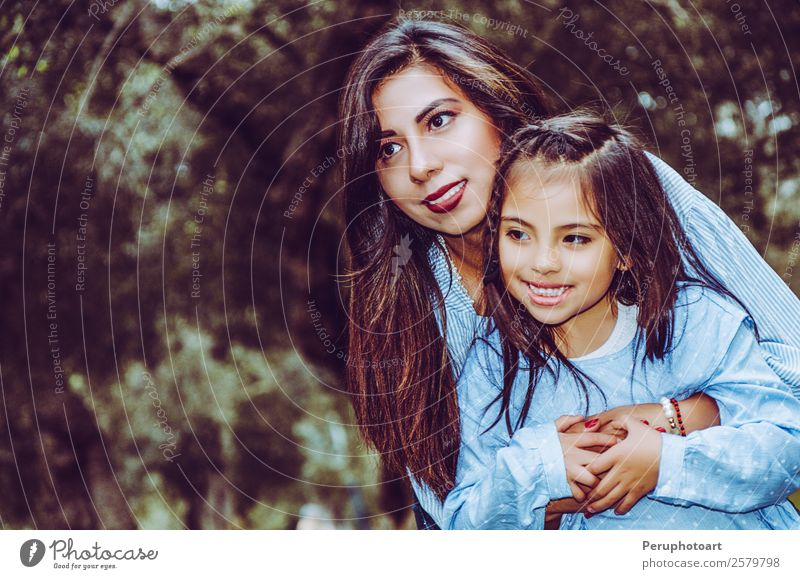 Mother carrying her cute and smiling daughter in the park Human being Feminine Child Baby Girl Young woman Youth (Young adults) Woman Adults Parents