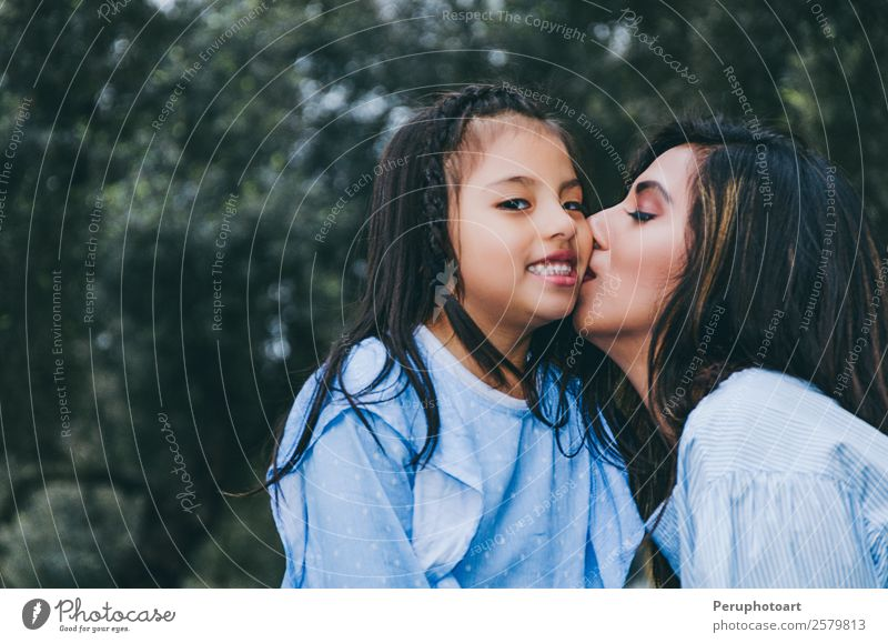 Happy mother kissing her daughter enjoying a winter afternoon Lifestyle Leisure and hobbies Summer Human being Feminine Child Baby Girl Young woman