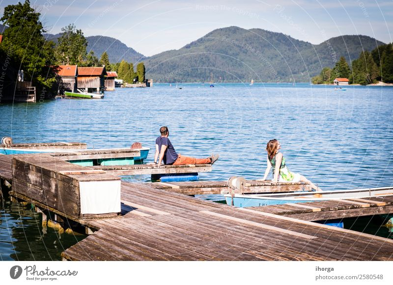 Two happy lovers on vacation at the pier on a lake Woman Human being Sky Vacation & Travel Nature Man Summer Beautiful Water Landscape Relaxation Forest