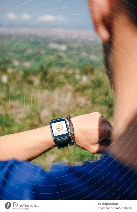 Sportsman looking a smartwatch Lifestyle Jogging Screen Technology Human being Man Adults Hand Nature Park Lanes & trails Heart Observe Fitness Authentic Smart