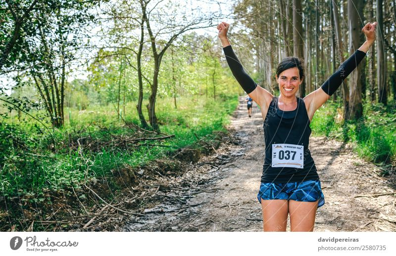 Young woman winning trail race Lifestyle Happy Feasts & Celebrations Sports Success Human being Woman Adults Nature Tree Forest Lanes & trails Sneakers Fitness