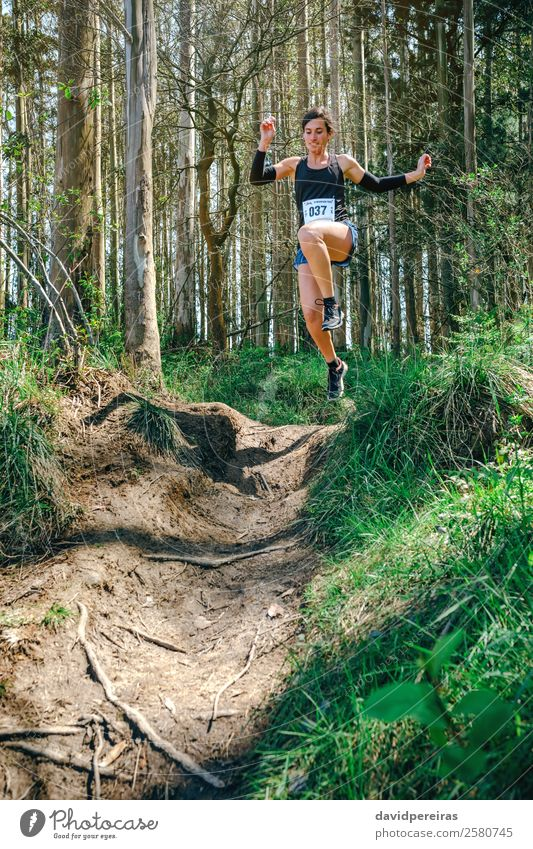 Woman jumping participating in trail race Lifestyle Sports Human being Adults Nature Tree Forest Lanes & trails Fitness Jump Authentic Speed Energy Competition