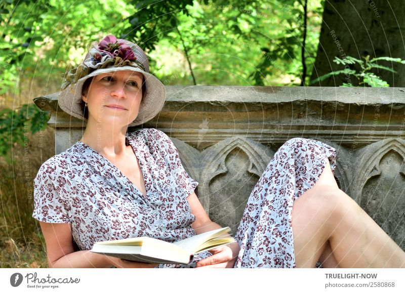 Woman with book and hat on historical stone bench Lifestyle Elegant Style Joy Beautiful Harmonious Well-being Contentment Relaxation Calm Leisure and hobbies