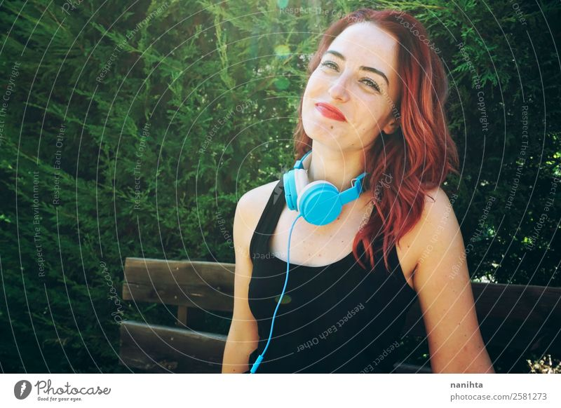 Smiley sporty woman in a park Lifestyle Style Joy Hair and hairstyles Healthy Athletic Wellness Well-being Leisure and hobbies Headset Headphones Technology