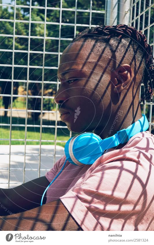 Young man alone listening to music Lifestyle Style Design Senses Relaxation Calm Leisure and hobbies Sun Headset Headphones Technology Entertainment electronics