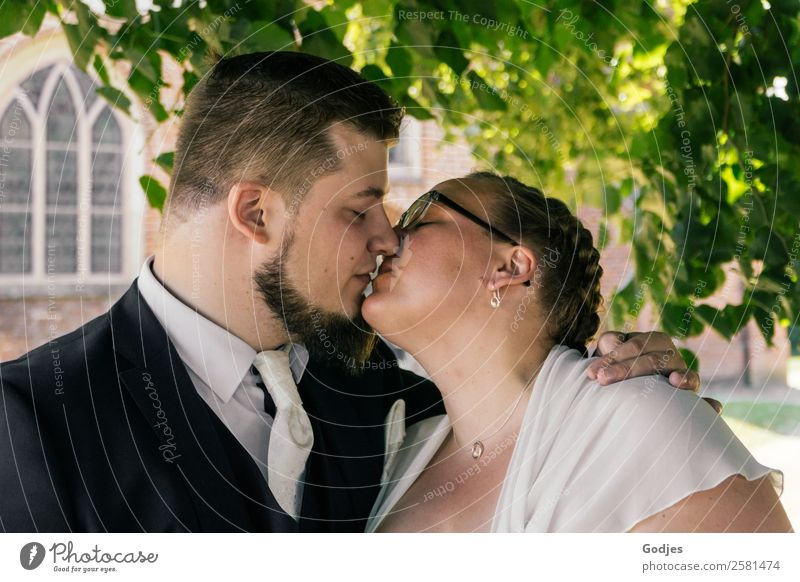Wedding couple kisses in front of the church Masculine Feminine Young woman Youth (Young adults) Young man 2 Human being 18 - 30 years Adults 30 - 45 years