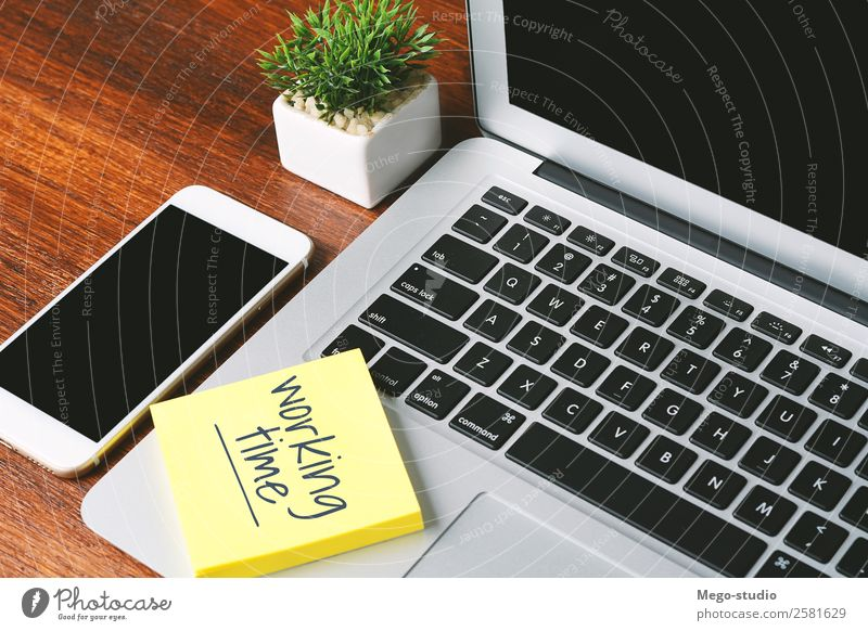 """Office desk table with paper sheet with """"working time"""" text. Clock Desk Table Work and employment Profession Workplace Business Telephone PDA Computer Notebook"""