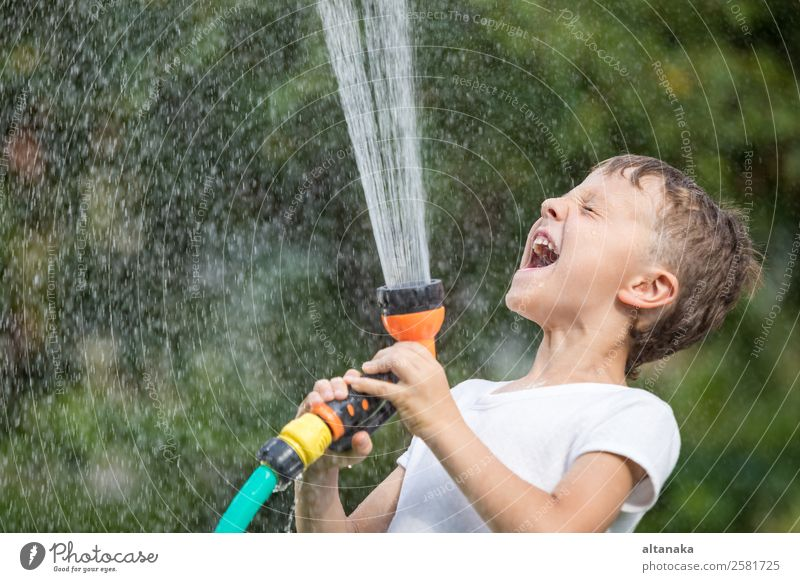 Happy little boy pouring water from a hose. Kid having fun outdoors. Joy Leisure and hobbies Playing Vacation & Travel Freedom Camping Summer