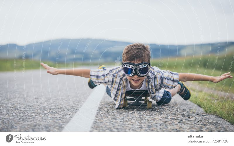Happy little boy playing on the road at the day time. Kid having fun outdoors. He skateboarding on the road. Concept of sport. Lifestyle Joy Playing