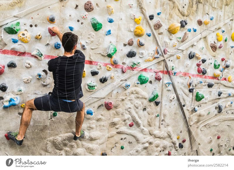 A Man practicing rock climbing on artificial wall indoors Lifestyle Joy Leisure and hobbies Sports Climbing Mountaineering Young man Youth (Young adults) Adults