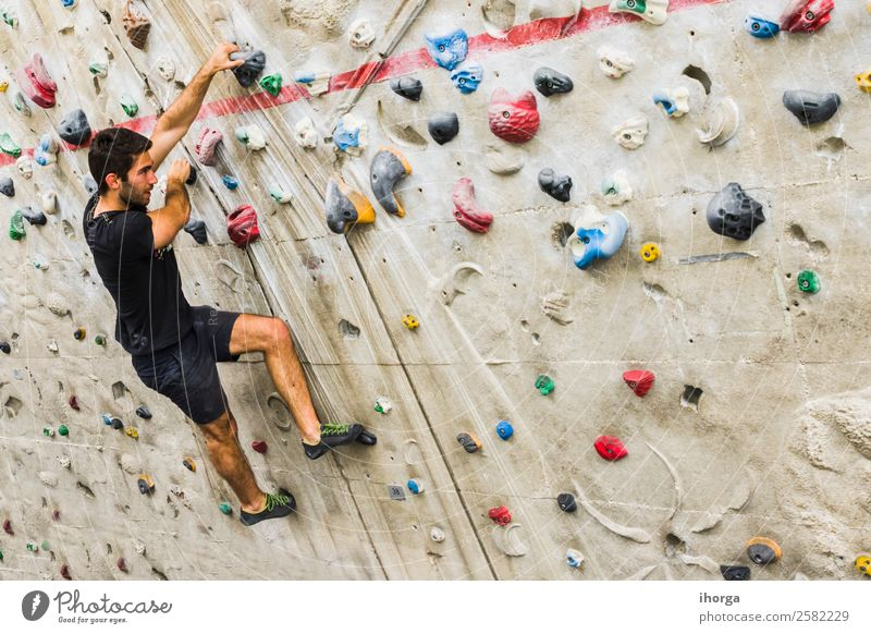A Man practicing rock climbing on artificial wall indoors Lifestyle Joy Leisure and hobbies Sports Climbing Mountaineering Adults 1 Human being 18 - 30 years