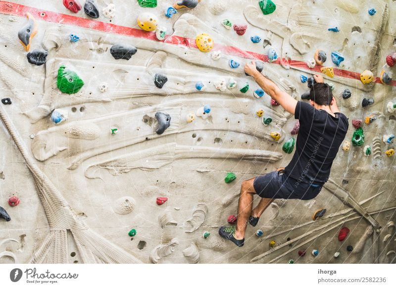 A Man practicing rock climbing on artificial wall indoors Lifestyle Joy Leisure and hobbies Sports Climbing Mountaineering Adults Hand Fingers Feet 1