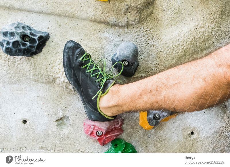 A Man practicing rock climbing on artificial wall indoors. Lifestyle Joy Leisure and hobbies Sports Climbing Mountaineering Masculine Adults Legs Feet