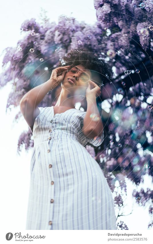 Happy young black woman surrounded by flowers Woman Blossom Spring Lilac Portrait photograph multiethnic Flower Black African Mixed race ethnicity Smiling