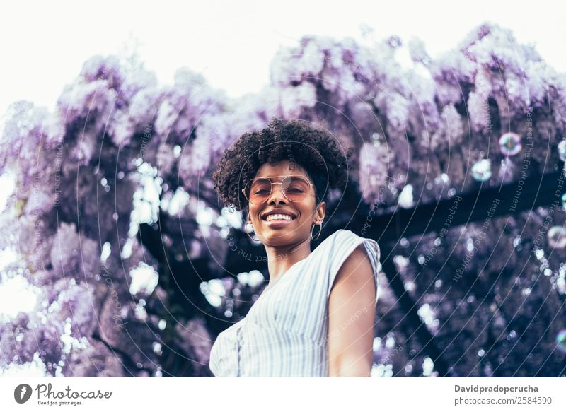 Happy young black woman surrounded by flowers Lifestyle Beautiful Relaxation Summer Garden Woman Adults Nature Tree Flower Blossom Dress Sunglasses Smiling