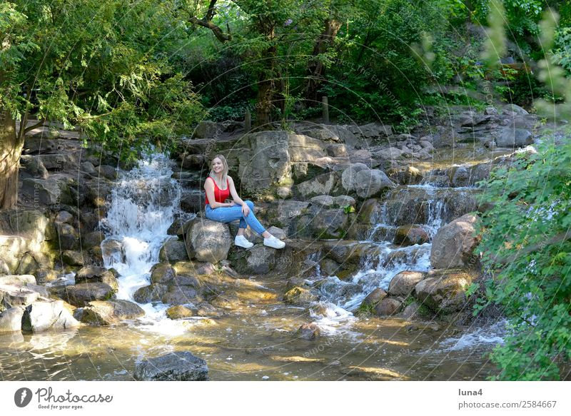 Woman sitting at the waterfall Lifestyle Joy Happy Beautiful Contentment Relaxation Leisure and hobbies Tourism Summer Young woman Youth (Young adults) Adults