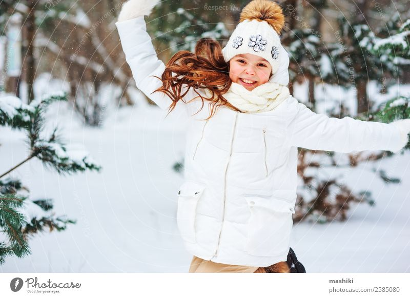 Winter portrait of happy child girl playing Child Nature Vacation & Travel Joy Forest Funny Snow Laughter Playing Freedom Fashion Snowfall Park Infancy