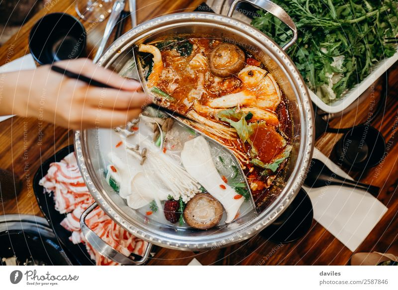 Korean hot pot meal, viewed from top, and one hand taking food from it with chopsticks. Food Meat Vegetable Soup Stew Eating Dinner Asian Food Pot Lifestyle