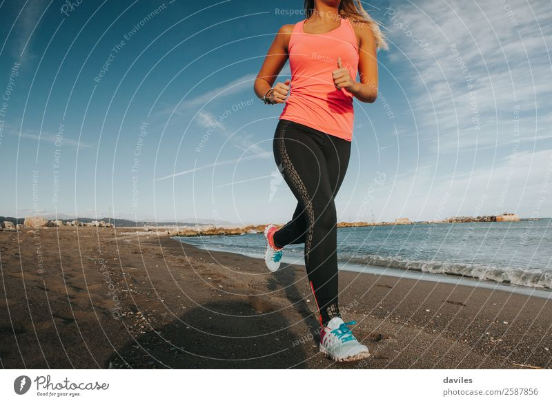 Woman with sports clothes running by the sea shore Lifestyle Health care Beach Ocean Sports Fitness Sports Training Sportsperson Jogging Human being Feminine