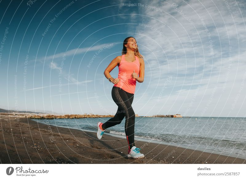 Woman with sports clothes running by the sea shore Lifestyle Athletic Fitness Wellness Beach Ocean Sports Sports Training Jogging Human being Feminine