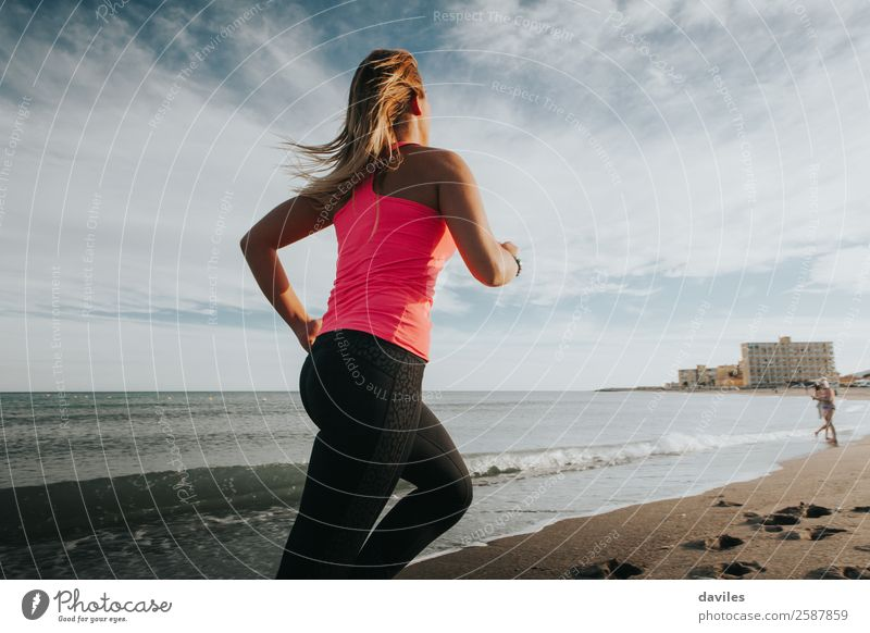 Woman with sports clothes running by the sea shore Lifestyle Joy Athletic Fitness Wellness Beach Ocean Sports Sports Training Jogging Human being Feminine