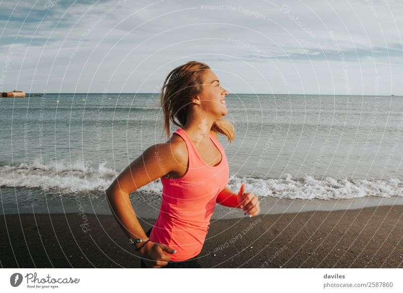 Woman with sports clothes running by the sea shore Lifestyle Joy Beautiful Athletic Fitness Wellness Summer Sun Beach Ocean Sports Jogging Human being Feminine
